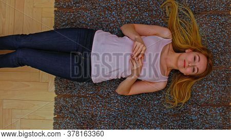 Young woman lying on floor in home. She daydreaming. camera is above her.