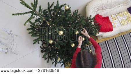 Woman is docorating fir on christmas tree. She is hanging golden baubles, christmas ornaments. It's christmas time. The time lapse movie.