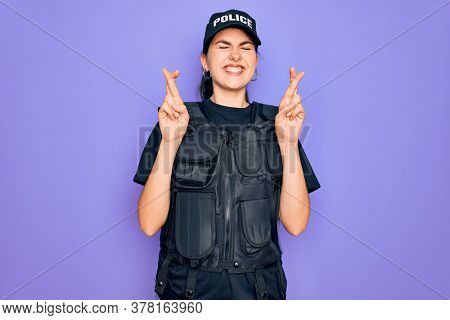 Young police woman wearing security bulletproof vest uniform over purple background gesturing finger crossed smiling with hope and eyes closed. Luck and superstitious concept.