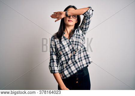 Young brunette woman with blue eyes wearing casual shirt and glasses over white background covering eyes with arm, looking serious and sad. Sightless, hiding and rejection concept