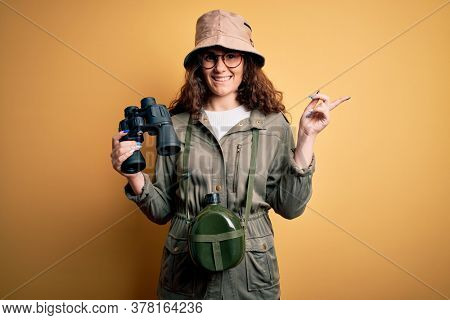 Beautiful tourist woman on vacation wearing explorer hat and water canteen using binoculars very happy pointing with hand and finger to the side