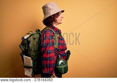 Middle age curly hair hiker woman hiking wearing backpack and water canteen using binoculars looking to side, relax profile pose with natural face and confident smile.