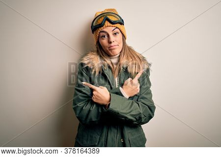 Young brunette skier woman wearing snow clothes and ski goggles over white background Pointing to both sides with fingers, different direction disagree