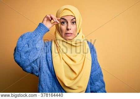 Young beautiful brunette muslim woman wearing arab hijab over isolated yellow background worried and stressed about a problem with hand on forehead, nervous and anxious for crisis
