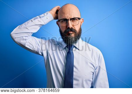 Handsome business bald man with beard wearing elegant tie and glasses over blue background confuse and wonder about question. Uncertain with doubt, thinking with hand on head. Pensive concept.