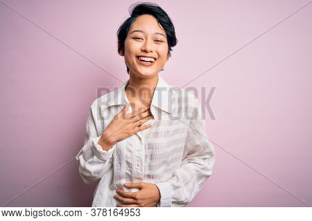 Young beautiful asian girl wearing casual shirt standing over isolated pink background smiling and laughing hard out loud because funny crazy joke with hands on body.