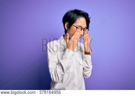 Young beautiful asian girl wearing casual shirt and glasses standing over purple background rubbing eyes for fatigue and headache, sleepy and tired expression. Vision problem