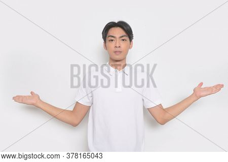 Young handsome man with wearing white polo shirt standing showing both hands open palms,