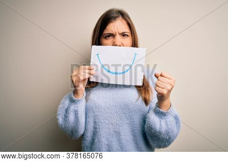 Young blonde woman holding funny smile drawing on mouth as happy expression annoyed and frustrated shouting with anger, crazy and yelling with raised hand, anger concept