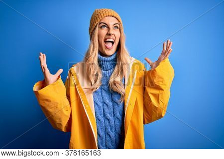 Young beautiful blonde woman wearing raincoat for rainy weather over blue background crazy and mad shouting and yelling with aggressive expression and arms raised. Frustration concept.