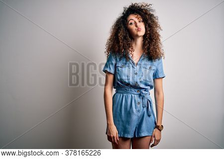 Young beautiful woman with curly hair and piercing wearing casual denim dress puffing cheeks with funny face. Mouth inflated with air, crazy expression.