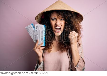 Young beautiful woman with curly hair and piercing wearing asian hat holding boarding pass annoyed and frustrated shouting with anger, crazy and yelling with raised hand, anger concept