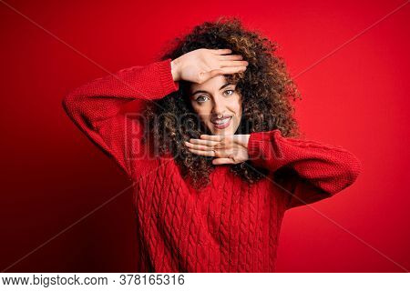 Young beautiful woman with curly hair and piercing wearing casual red sweater Smiling cheerful playing peek a boo with hands showing face. Surprised and exited