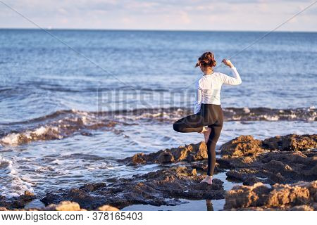 Young beautiful sportwoman practicing yoga. Coach teaching postures at the beach
