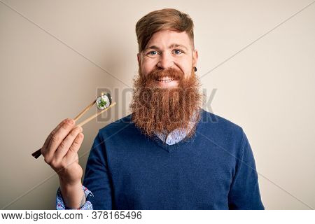 Redhead Irish man with beard eating green maki sushi using chopsticks over yellow background with a happy face standing and smiling with a confident smile showing teeth