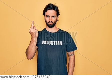 Young handsome hispanic volunteer man wearing volunteering t-shirt as social care Showing middle finger, impolite and rude fuck off expression