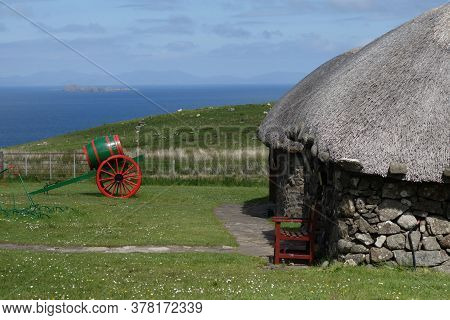 Historic And Rustic Cabin With A Bench In The Front And A Cannon Under The Blue Sky And The Sea In T