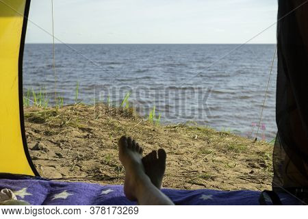 Camping Man Lying In A Tent Close-up Of His Feet . Relaxing On The Beach.