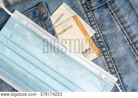 Close-up Of A Protective Medical Mask And Euro Banknotes In The Pocket Of Blue Old Jeans On A Gray W