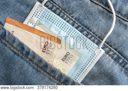 Close-up Of A Protective Medical Mask And Money In The Pocket Of Old Jeans On A Wooden Background. G