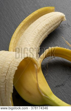 Ripe Yellow Banana With Half Peeled Peels On A Gray Stone Dark Board. Vertical View. Diet Concept