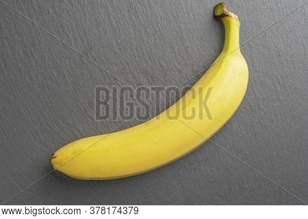 Ripe Unpeeled Banana With Bright Yellow Peel On A Stone Surface. Gray Textured Board. Tropical Ingre