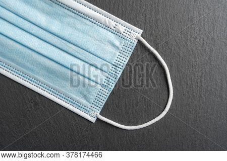 Close-up Medical Disposable Mask. Protective Surgical Blue Mask On A Dark Gray Stone Background. Col