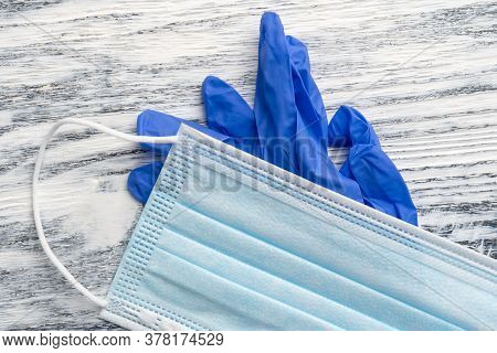 Medical Protective Mask And Nitrile Blue Gloves On A Wooden Background. Protective Hygiene Kit. Coro