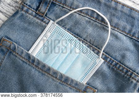 Medical Protective Surgical Mask In A Pocket Of Blue Jeans Close-up. Coronavirus Protection Concept