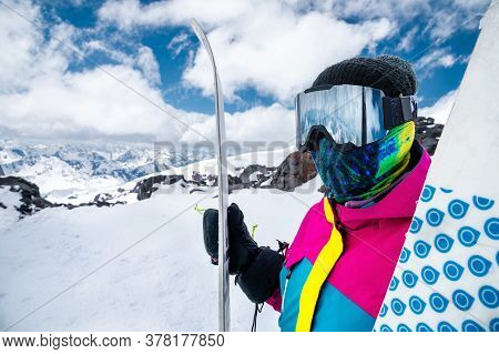 Portrait Of A Girl Skier In A Multi-colored Bright Jacket In A Ski Mask With Her Face Closed On A Su