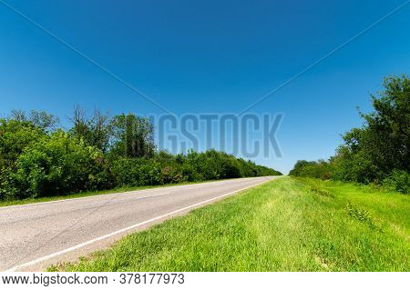 Country Asphalt Road In Summer With Green Grass And Trees On The Roadsides Against The Blue Sky. Sun