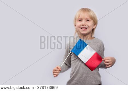 Exciting Fair-haired Boy Holding Flag Of France. Learning French For Children. Education In France