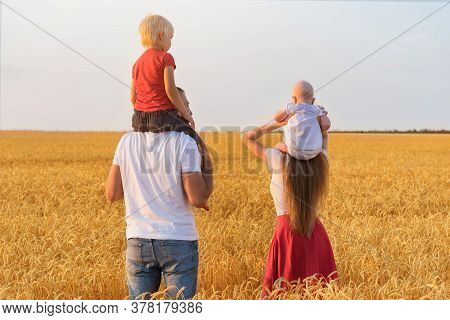 Young Family In Field With Two Young Children. Kids Sit On Shoulders Of Parents. Rear View