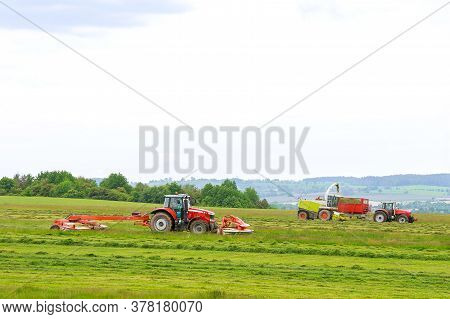 Big Red Tractor With Two Mowers Mows The Grass For Silage