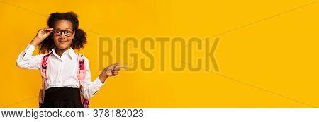 Look Here. Adorable Black Schoolgirl Pointing Finger Aside Advertising Something Standing Over Yello