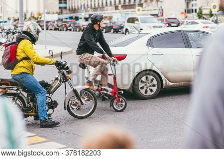 Moscow, Russia July 7, 2017: Young Man In A Helmet And A Yellow Jacket Sits On A Motorcycle On A Ped