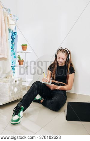 Depressed Teenage Girl Sitting On The Floor In Her Closet, Listening To Music In Headphones And Writ