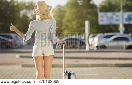 Catching A Cab. Rear View Of Female Traveller Standing Near Airport, Waving Hand, Calling Taxi Drive