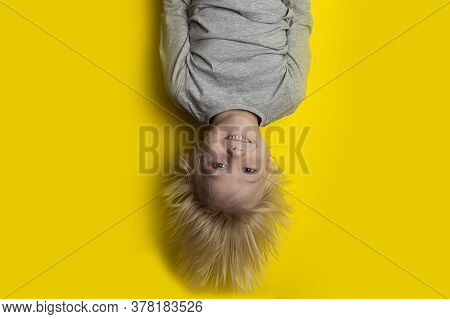 Smiling Fair-haired Boy Hanging Upside Down On Yellow Background