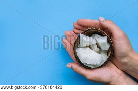 Halved Fresh Coconut And Coconut Flesh On The Blue Background. Coconut In Hands