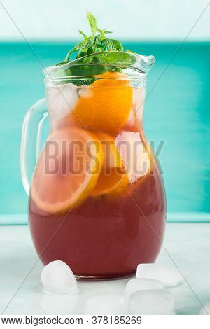 Fresh Red Cocktail Mocktail Sangria In Transparent Glass Pitcher With Ice, Mint Leaves And Lemon And