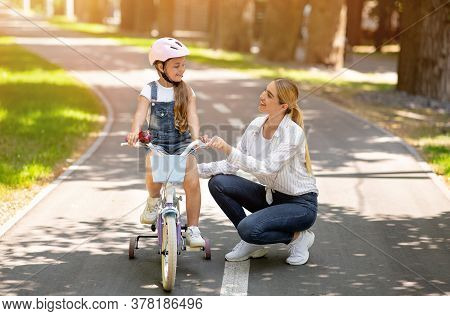 Mother Teaching Daughter To Ride A Bike Encouraging Her Standing In Park Outdoors. Family Weekend An