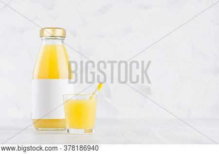 Fresh Orange Juice In Glass Bottle With Blank Label Mock Up With Wine Glass, Straw On Wood Table In