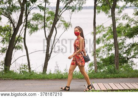 COVID-19 Mandatory mask wearing in urban city young Asian woman walking with face protection wear as prevention for corona virus outside park summer lifestyle. Coronavirus.