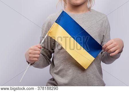 Child Holds The Ukrainian Flag. Close Up. Learning Ukrainian For Children. Education In Ukraine.