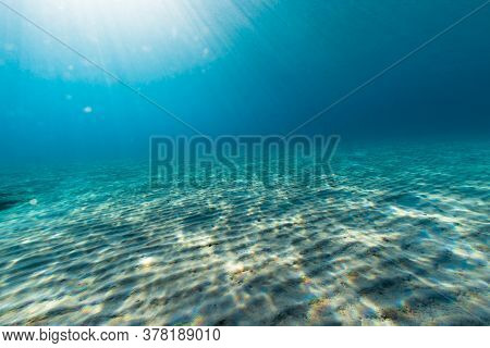 Underwater Shot Of Sand Sea Bottom With Sun Beams