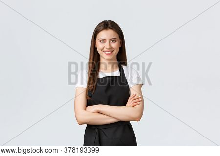 Cheerful Smiling Female Barista In Black Apron Cross Arms Chest, Looking Ready And Confident. Young