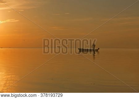 Fisherman At The Boat On Golden Sunset Sea. Beautiful And Romantic Sunset. Silhouette Of Fishermen W