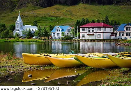 Yellow Kayak Boats With The Blue Church And Houses In The Background, Seydisfjordur, Iceland. Focus