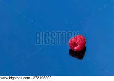 Ripe Juicy One Raspberry With Hard Shadow On Blue Mirror Background. Single Object Photo